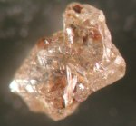 MSC-DG -342: Light brown aggregate with inclusions. Red iron oxide stains are on the surface.